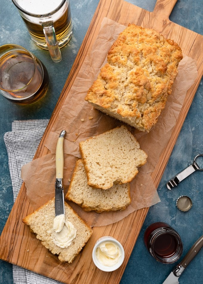 beer bread on a wood serving board with butter and glasses of lager