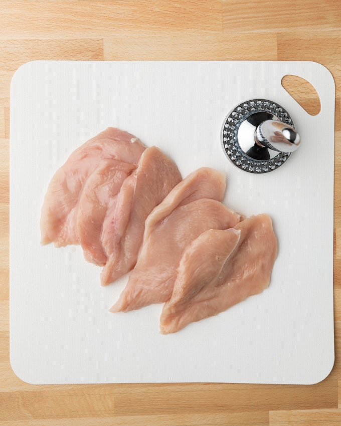chicken cutlets on a white cutting board with a meat mallet