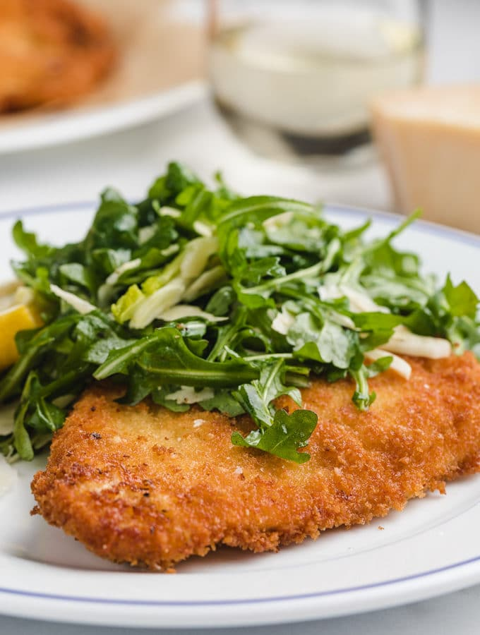 chicken milanese on a white plate with arugula salad