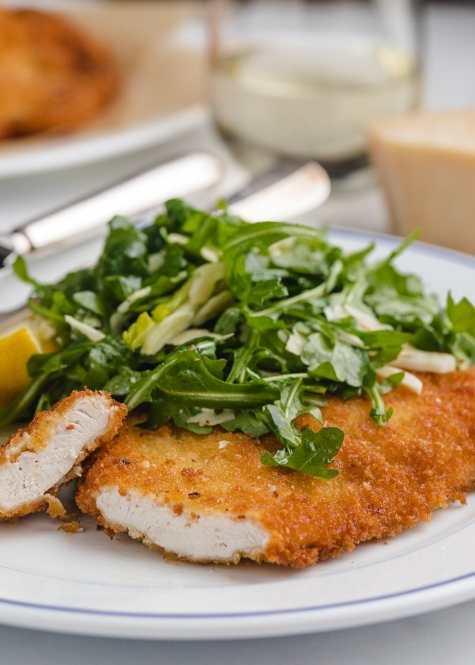sliced chicken milanese cutlet on a white plate
