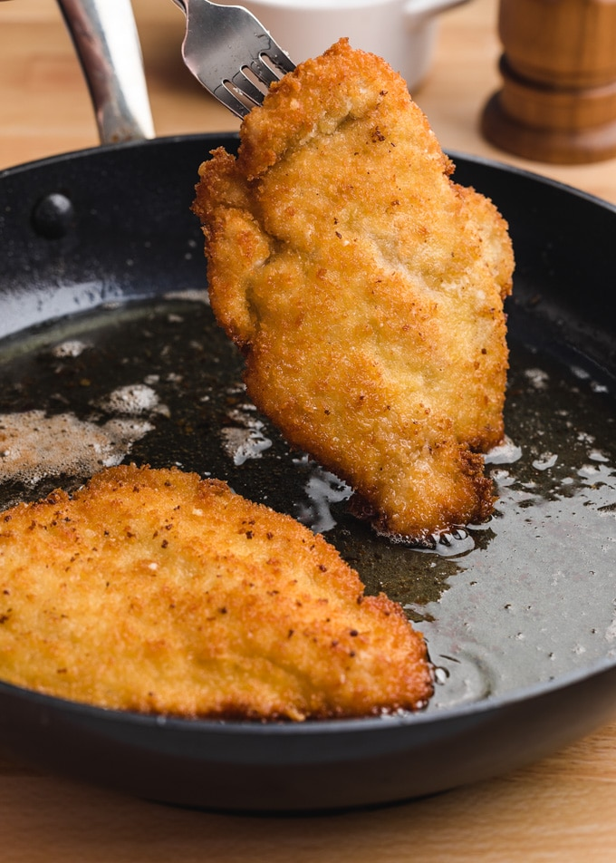 breaded chicken cutlets fried in olive oil in a skillet