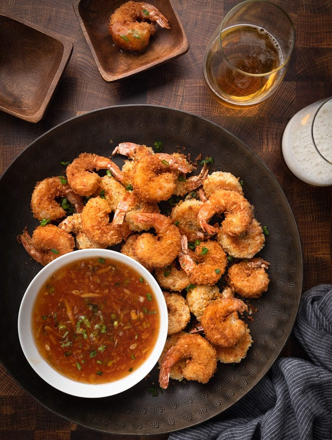 coconut shrimp on a bronze serving platter with spicy orange dipping sauce