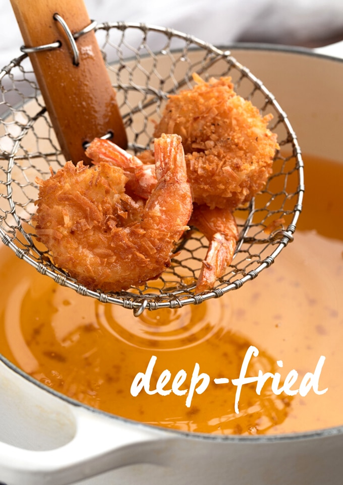 deep-fried coconut shrimp in a spider strainer over a pot of hot oil