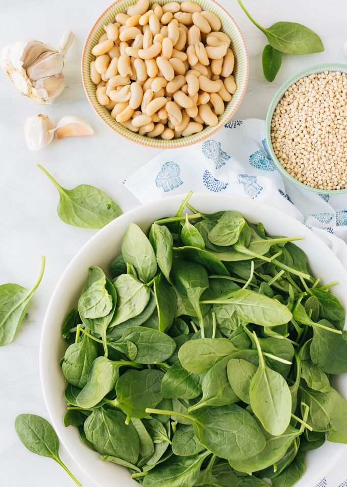 overhead view of bowls of baby spinach, cannellini beans, and dried Israeli couscous
