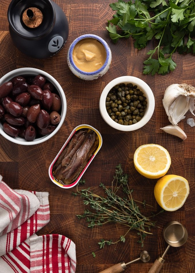 overhead photo of olives, capers, anchovies, lemon wedges, herbs, garlic, and Dijon mustard