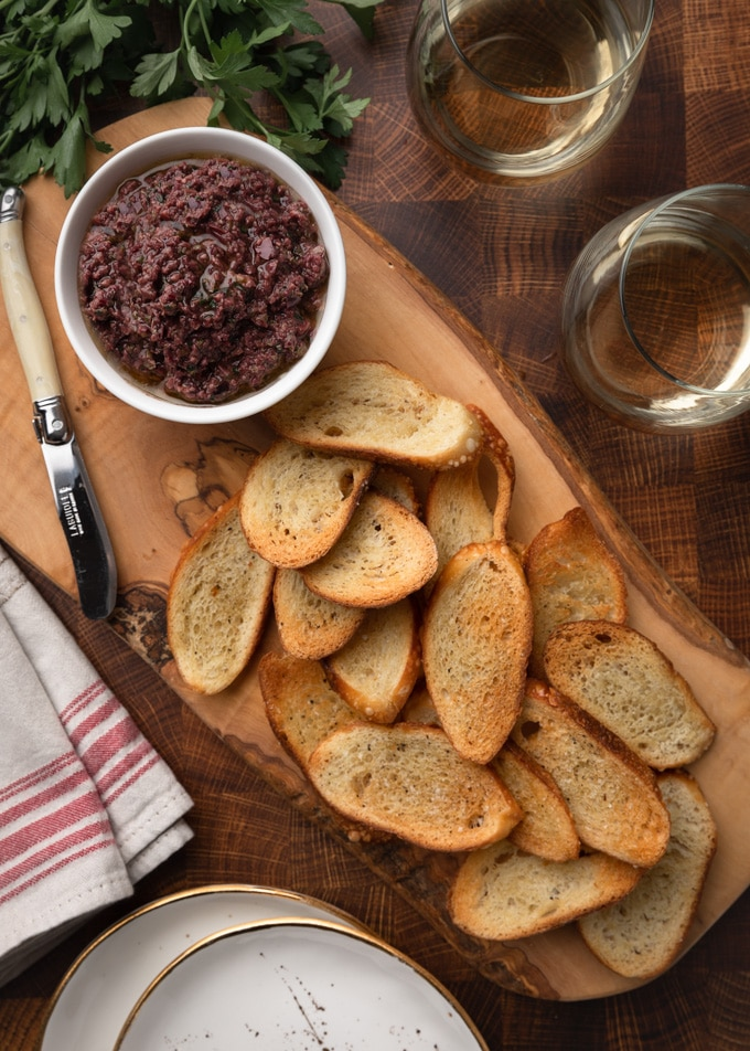 tapenade served with crostini on a wood board