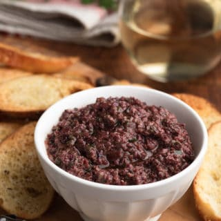 black olive tapenade in a white bowl on a serving board with crostini