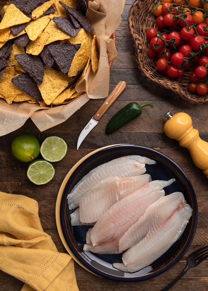 raw tilapia fillets on a plate next to a baskets of tortilla chips and cherry tomatoes on the vine