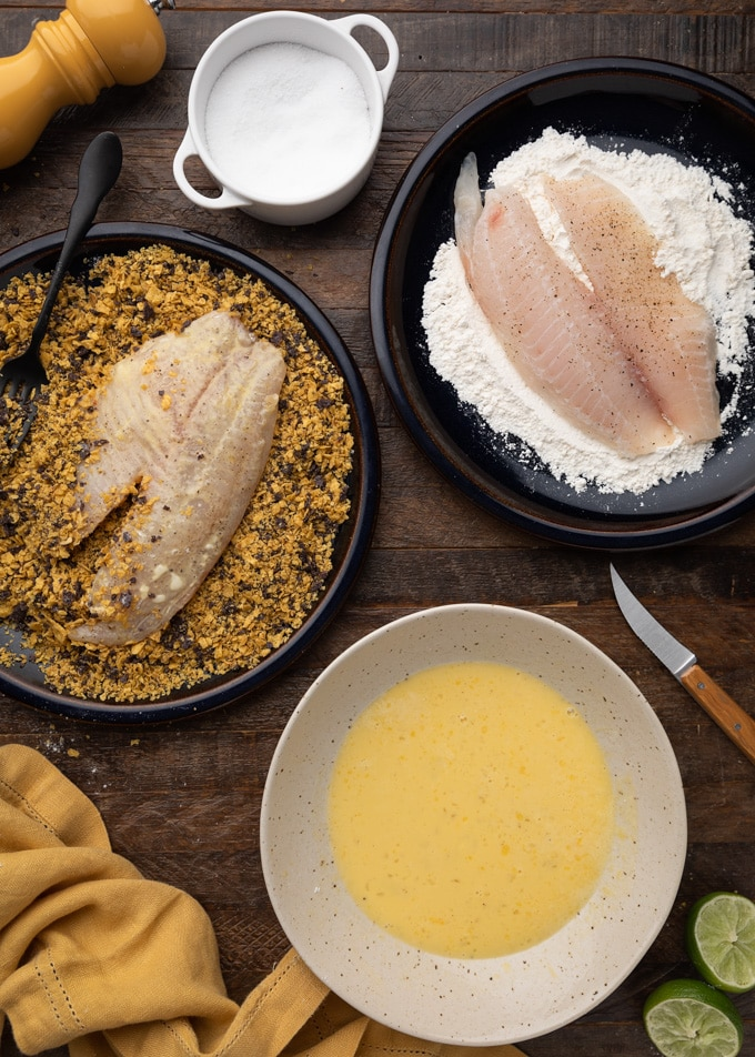 overhead photo showing tilapia fillets being breaded with flour and crushed tortilla chips