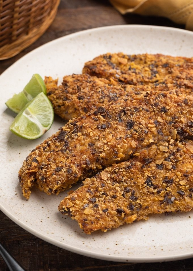 pan-fried tortilla chip breaded tilapia fillets on an ivory plate