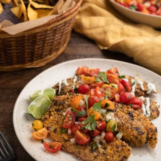fried tortilla chip crusted tilapia fillets on an ivory plate with cherry tomato pico de gallo