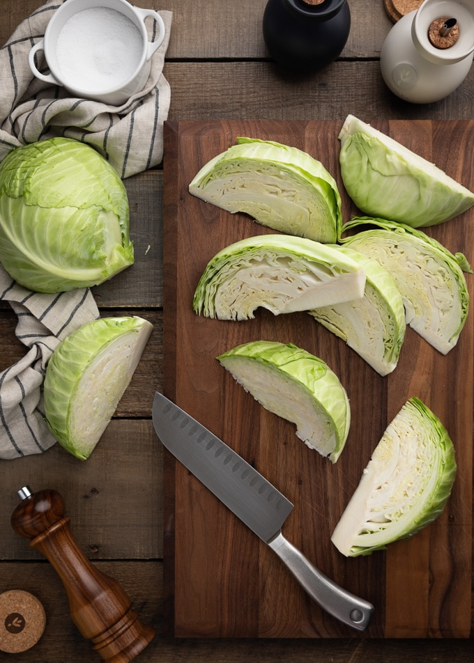 green cabbage wedges on a wood cutting board with a santoku knife