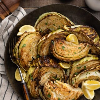 roasted cabbage with lemon wedges in a dark bronze serving bowl