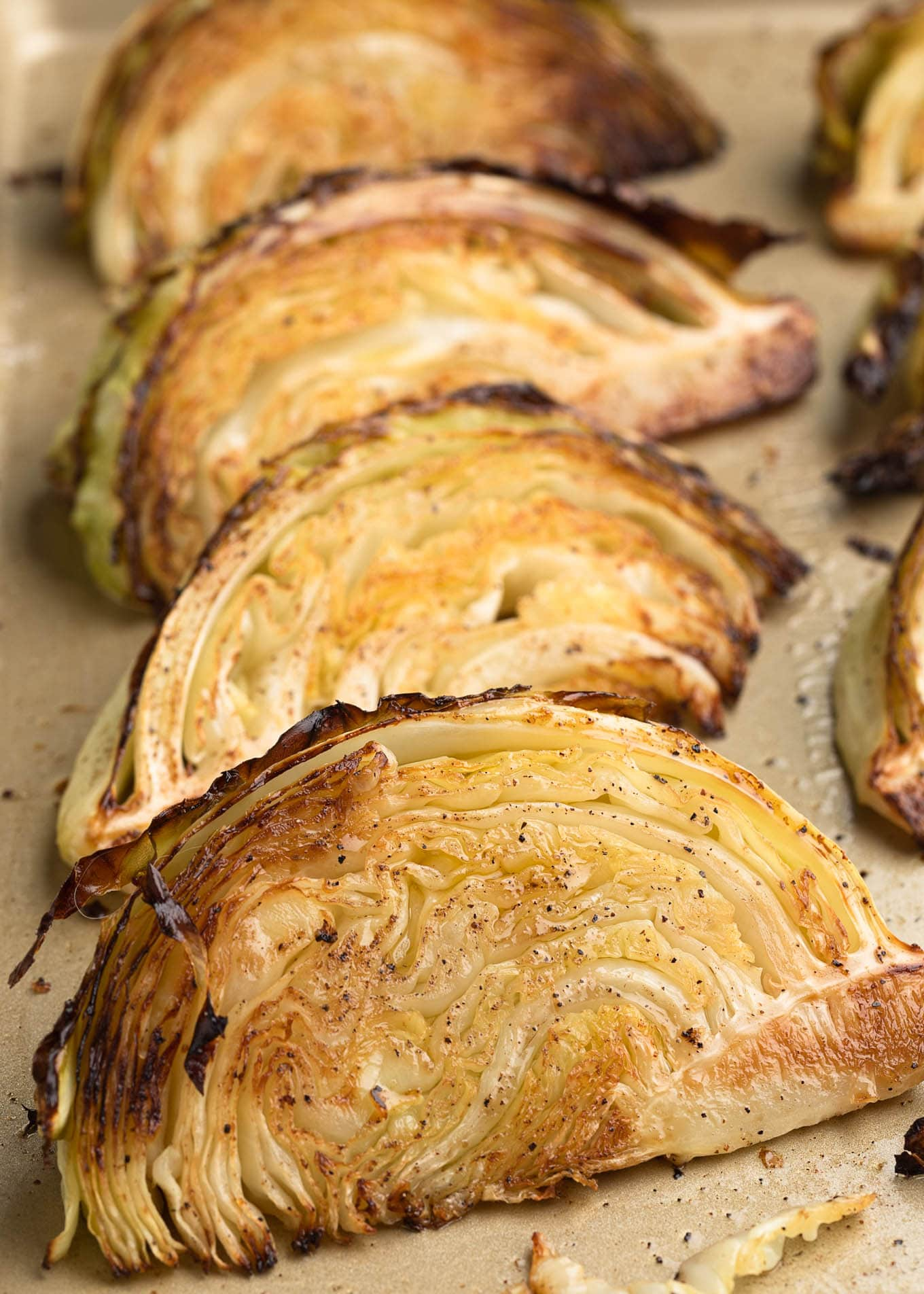 caramelized cabbage wedges on a baking sheet
