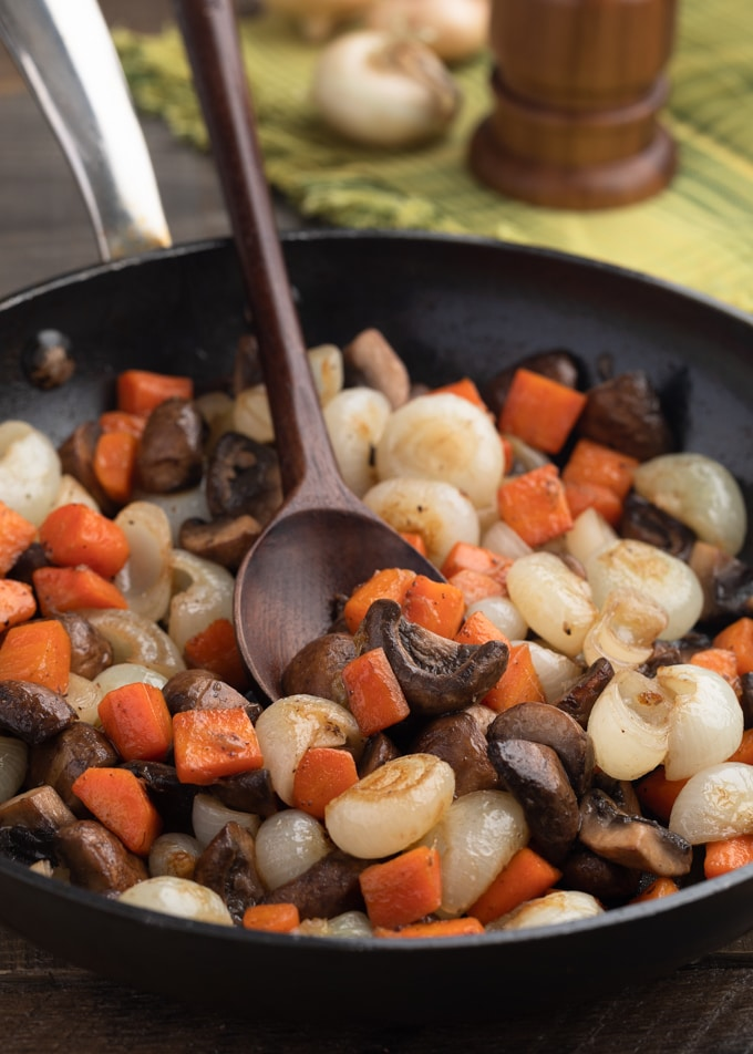 carrots, cremini mushrooms, and cippolini onions in a saute pan with a wooden spoon