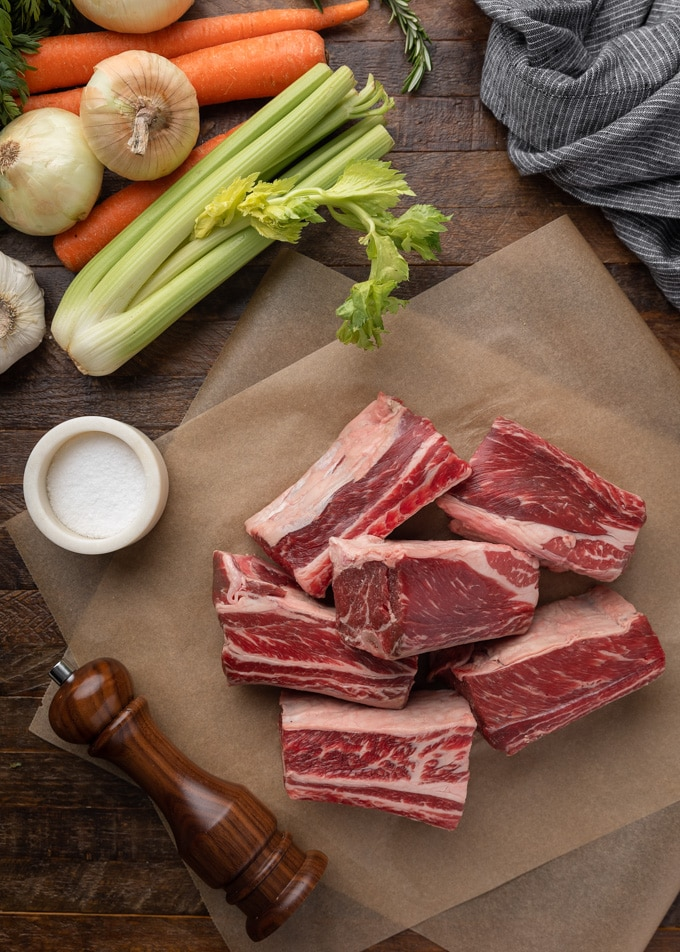 raw short ribs on parchment paper, surrounded by celery, onions, carrots, a salt crock, and wood pepper grinder