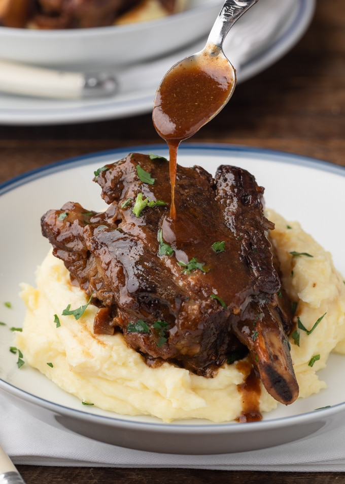 drizzling stout gravy over a braised short rib with mashed potatoes