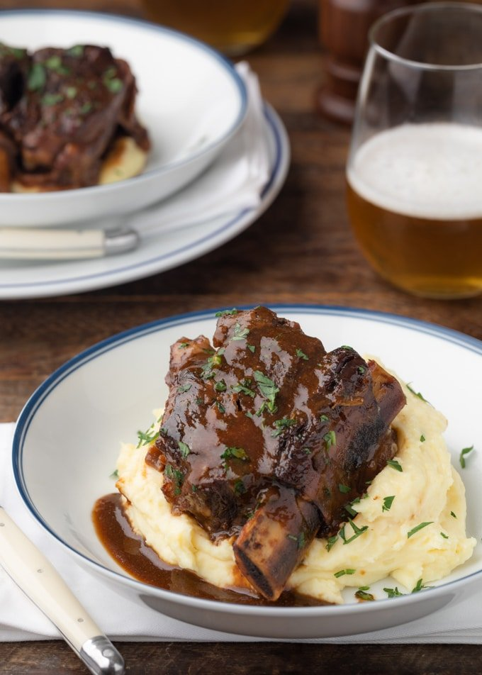 stout beer braised short rib in a white serving bowl over mashed potatoes