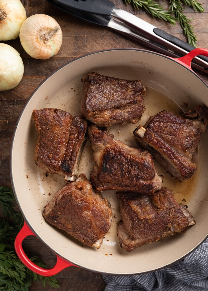 seared short ribs in an enameled cast iron Dutch oven