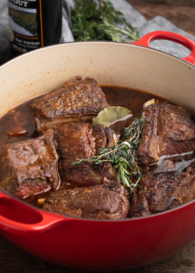 seared short ribs in an enameled cast iron Dutch oven with herbs and braising liquid