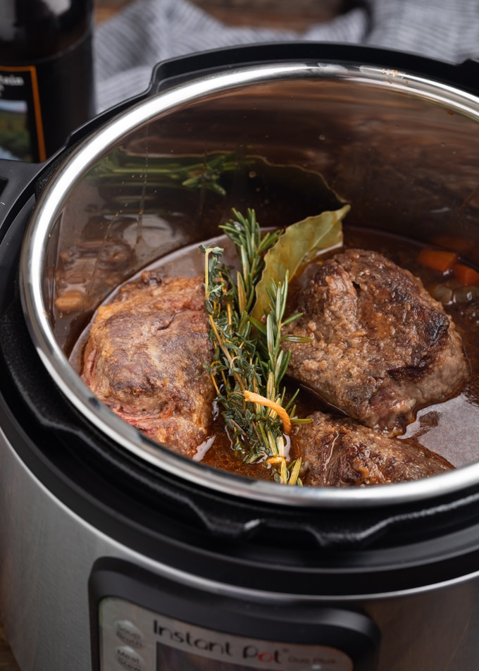 seared short ribs with stout braising liquid and fresh herbs in an electric pressure cooker