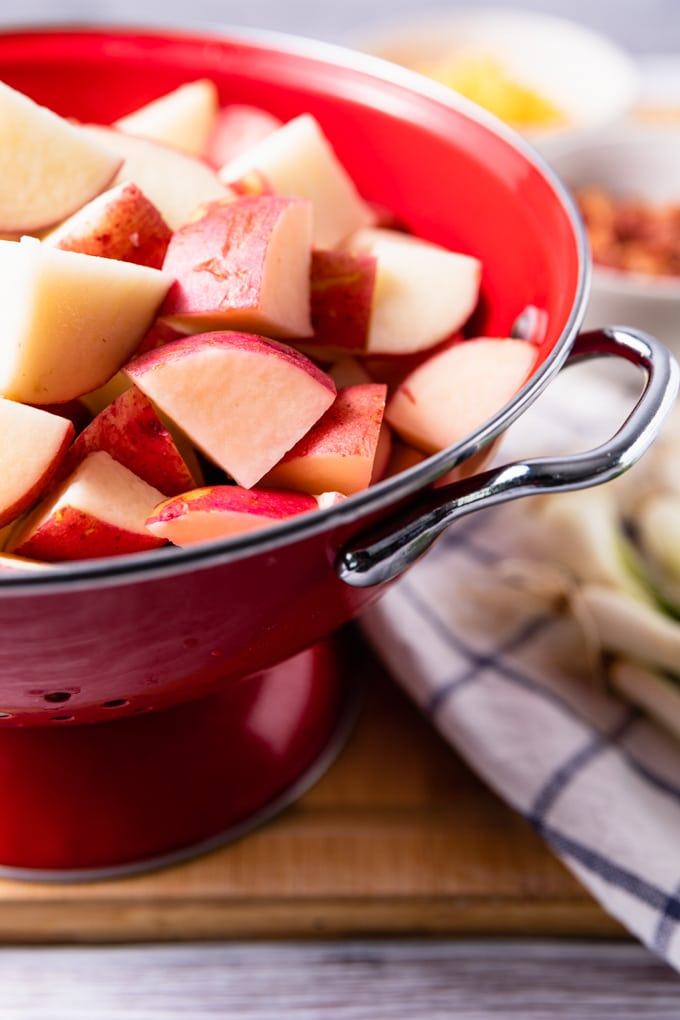 cubed raw red potatoes in a red colander