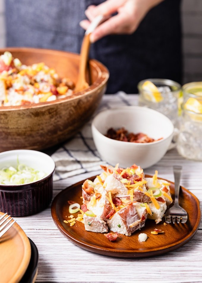 loaded potato salad with bacon and cheddar on a wooden plate, surrounded by bowls of scallions, bacon, and a large serving bowl