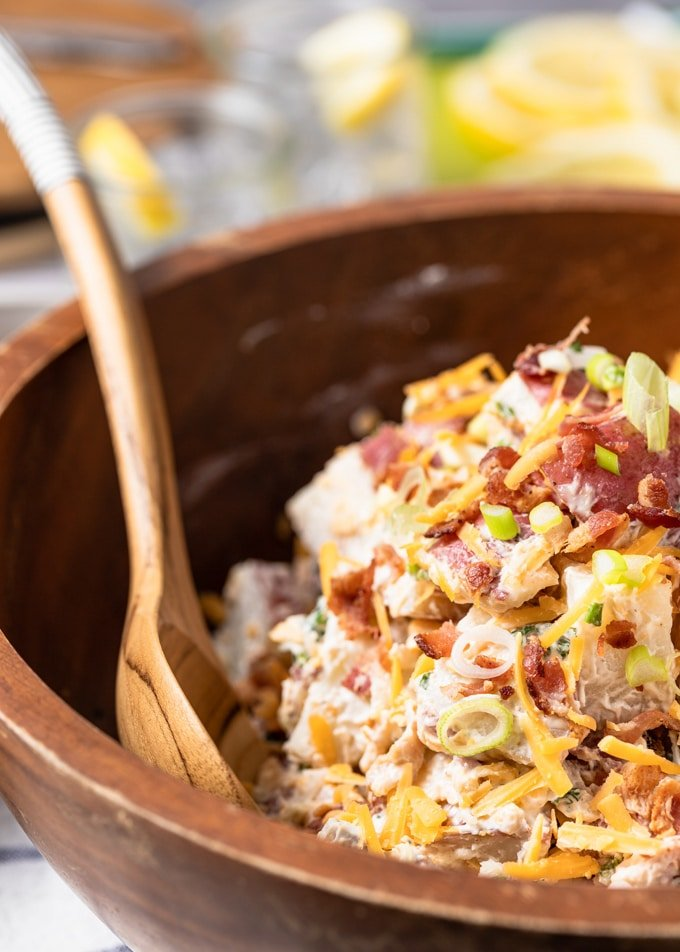 side view of loaded potato salad in a wooden bowl with a wooden serving spoon