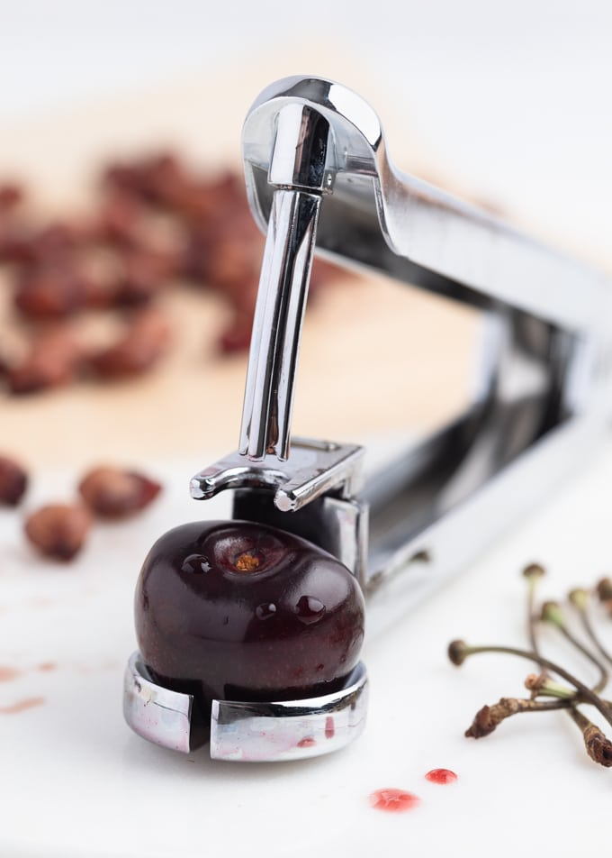 Closeup of a sweet cherry sitting in a handheld cherry pitter on a marble cutting board