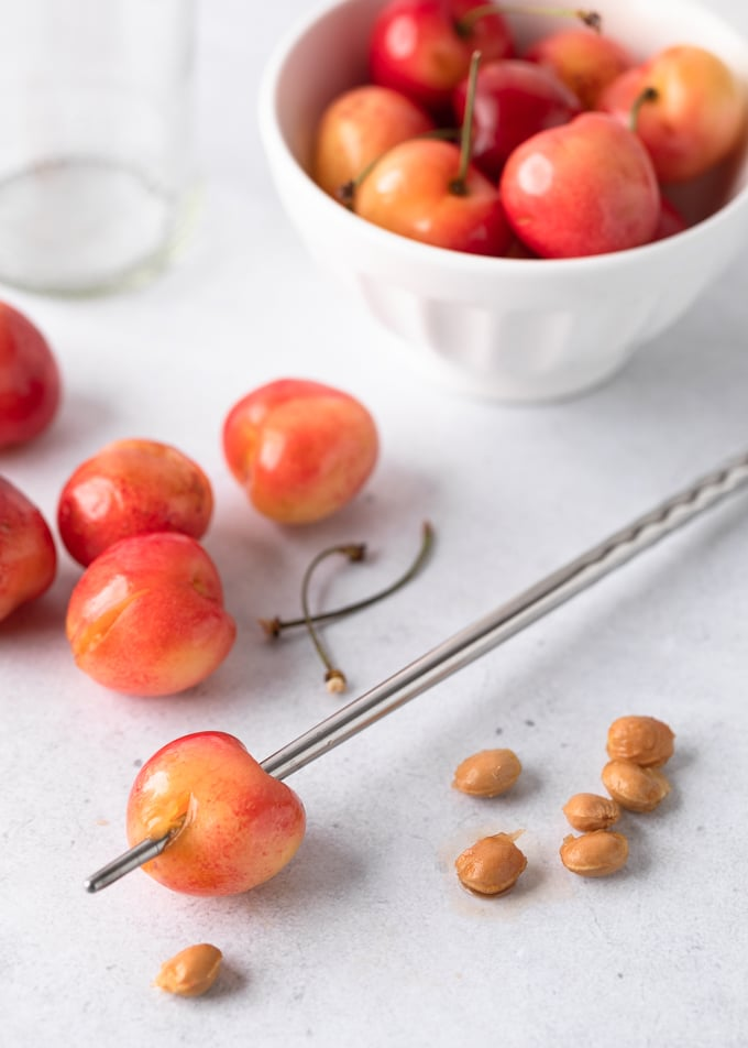 A Rainier cherry skewered with a metal chopstick next to a pile of cherry pits, pitted cherries, and a bowl of whole cherries