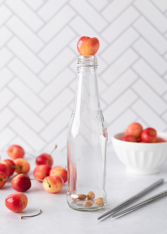 A rainier cherry sitting on top of a glass soda bottle holding cherry pits in the bottom, surrounded by more cherries and a pair of metal chopsticks.