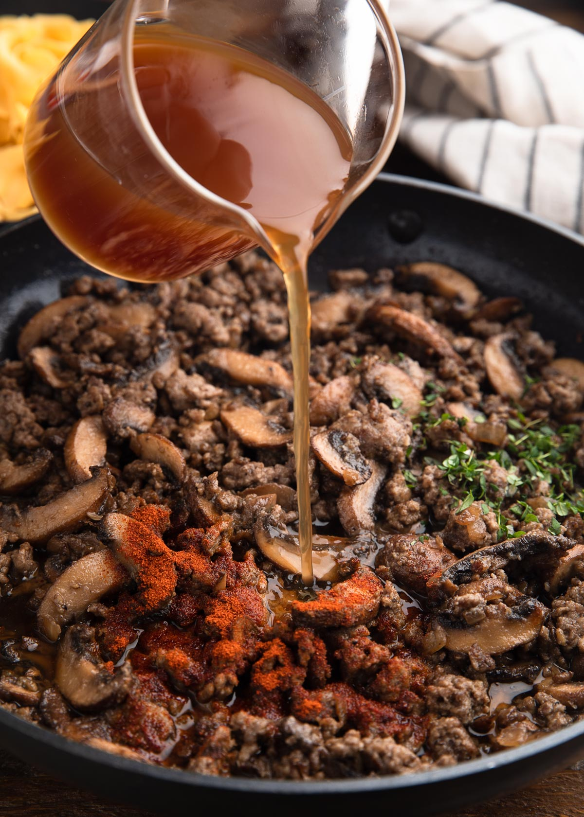 pouring beef broth into a saute pan with ground beef, mushrooms, paprika, and herbs