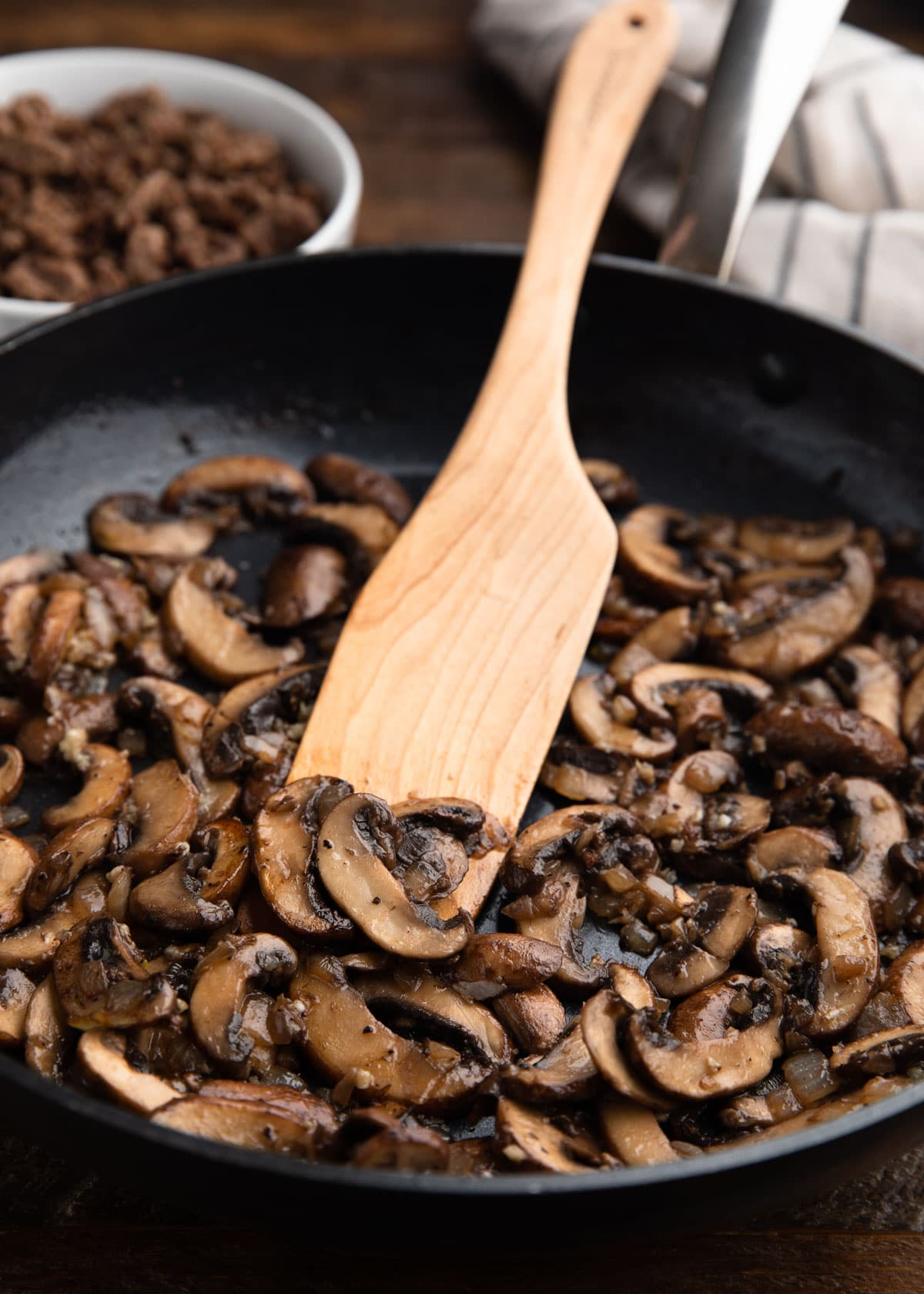 sauteed mushrooms in a nonstick skillet with a wooden spoon