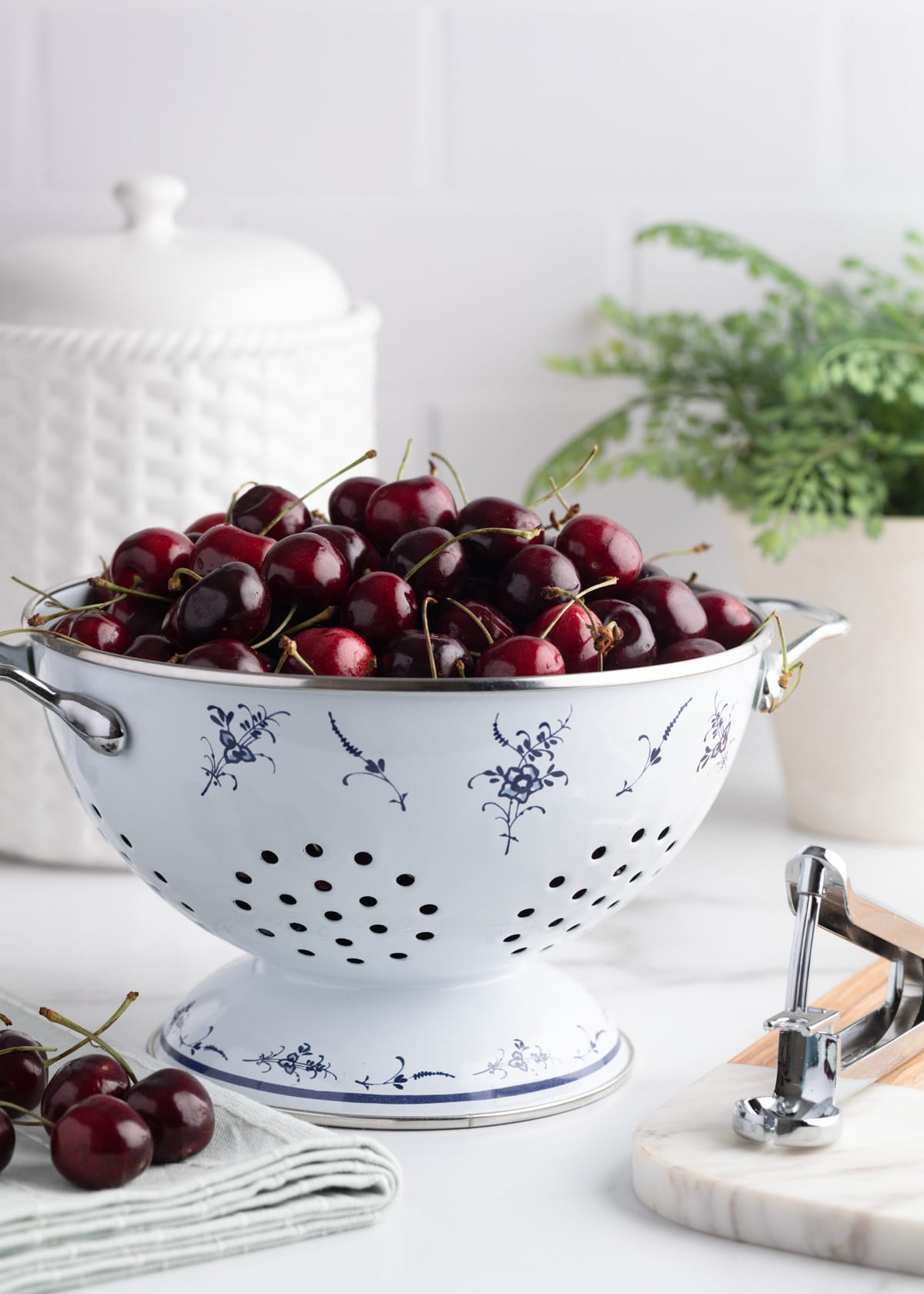 fresh bing cherries in a white enameled colander, on a marble countertop against a white subway tile kitchen background