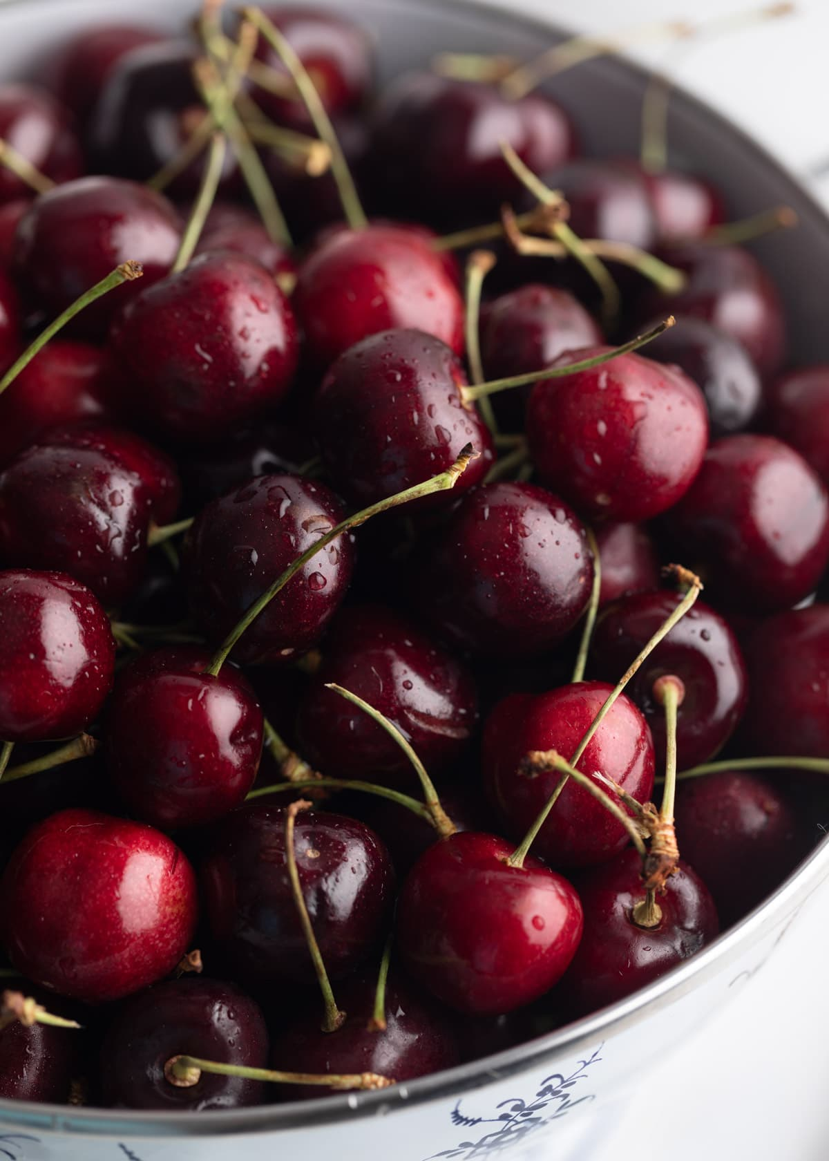 closeup photo of fresh Bing cherries in a white enameled colander