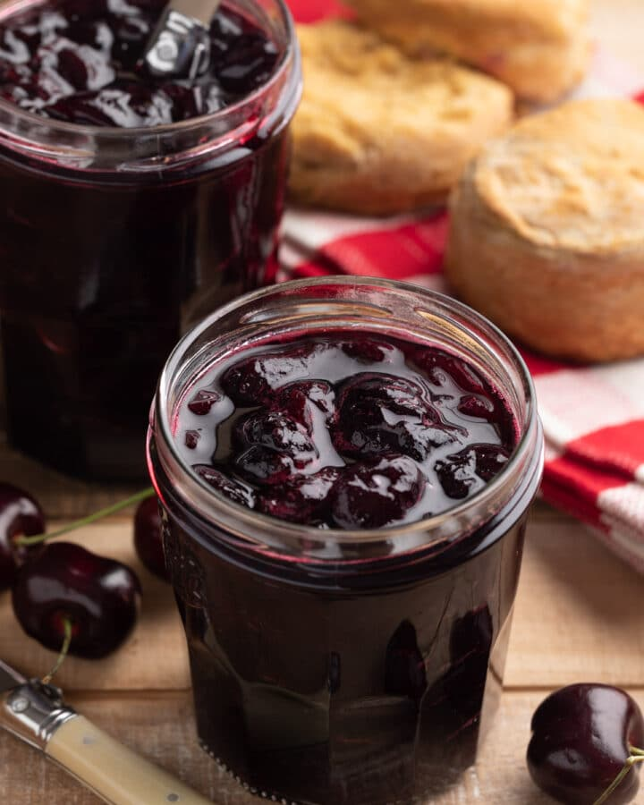 no-pectin cherry preserves in glass jam jars on a wood board