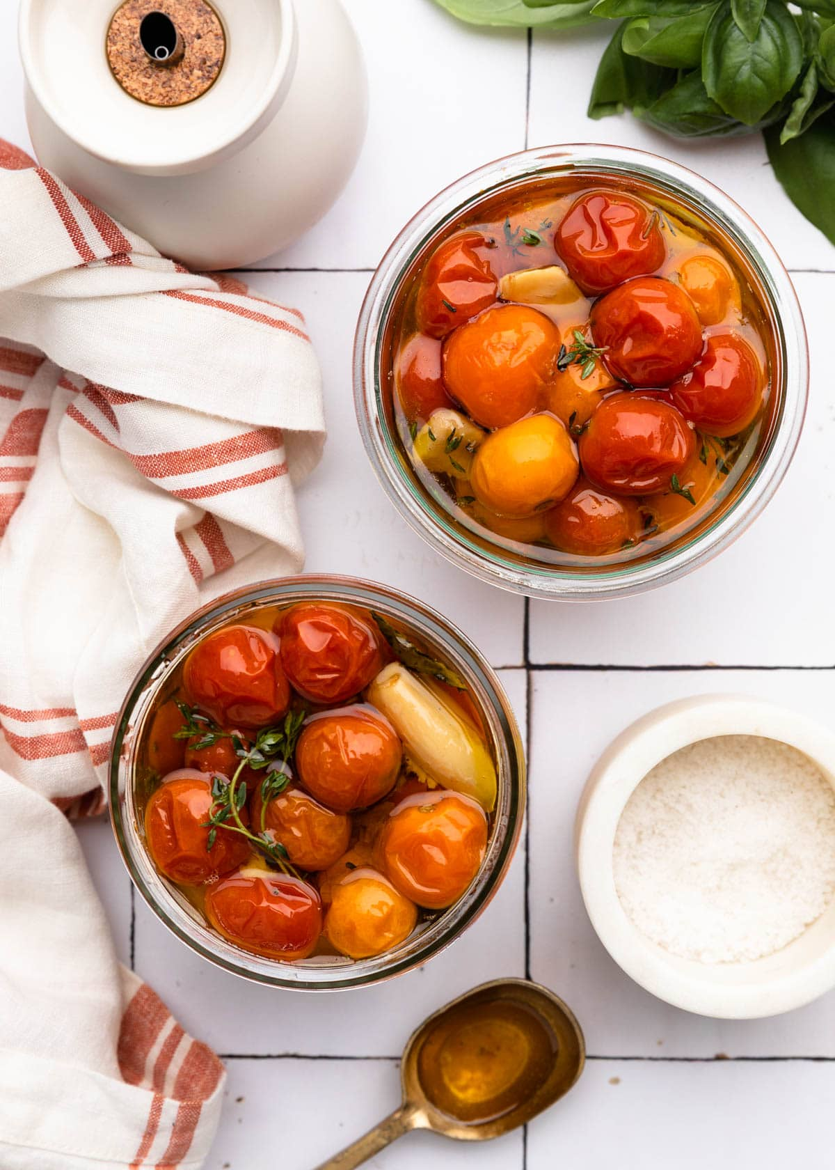 overhead of two jars of cherry tomato confit on a white tile board