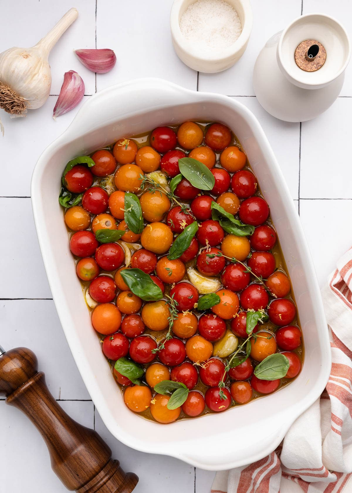 overhead of cherry tomatoes in a white ceramic baking dish with fresh herbs