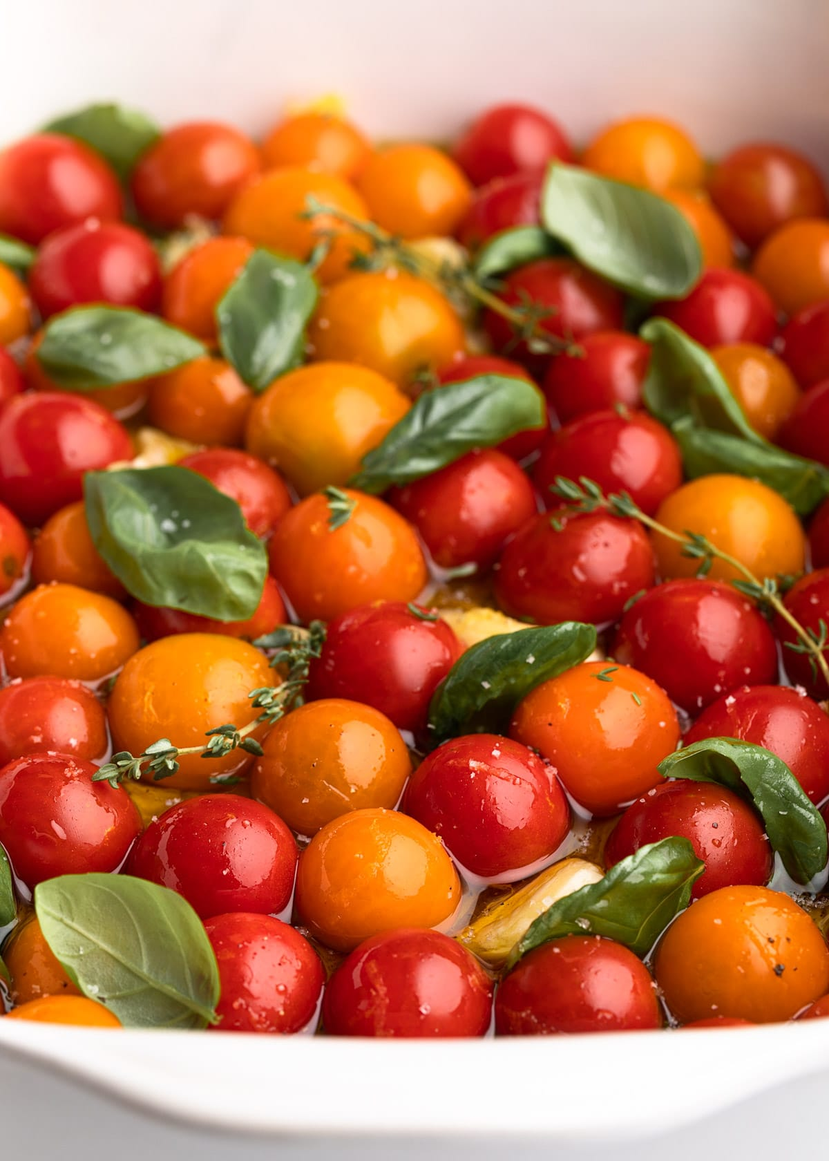 cherry tomatoes in a white ceramic baking dish with olive oil, garlic, and fresh herbs