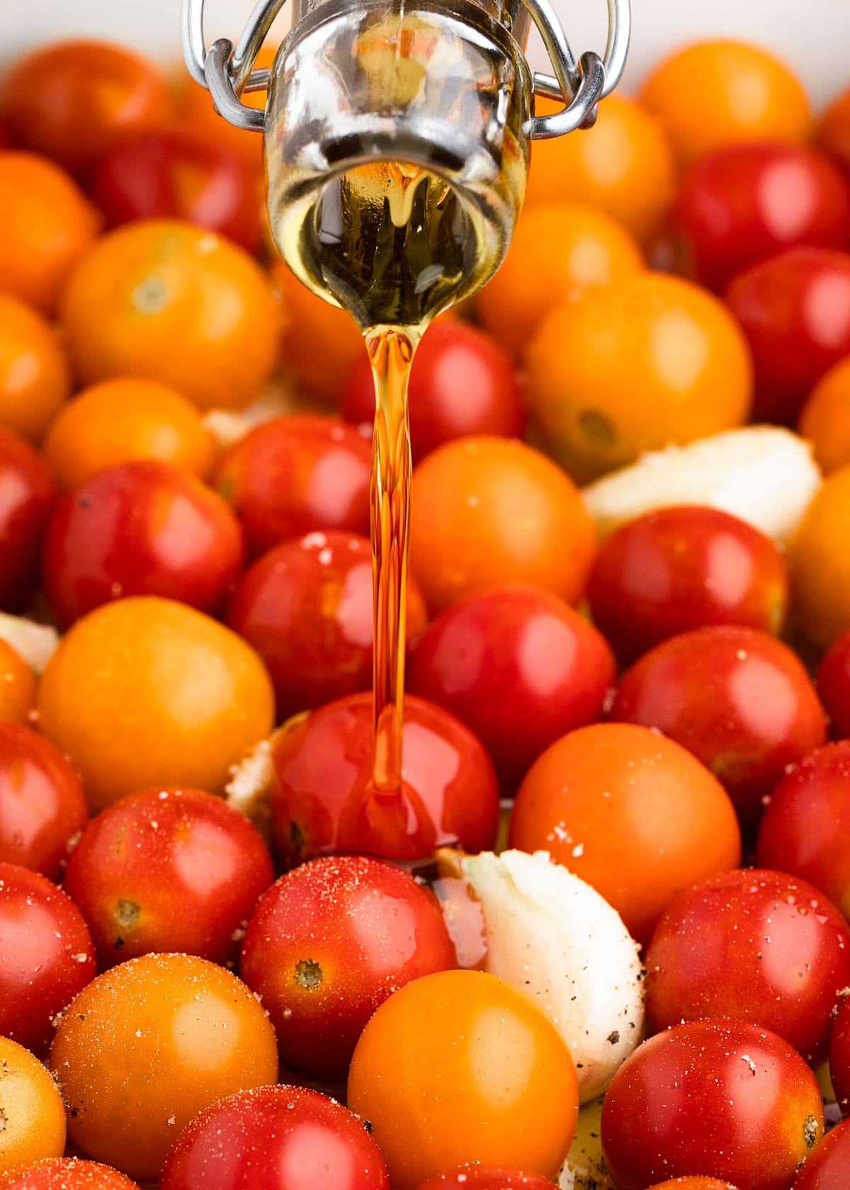 pouring olive oil into a pan of cherry tomatoes and garlic cloves