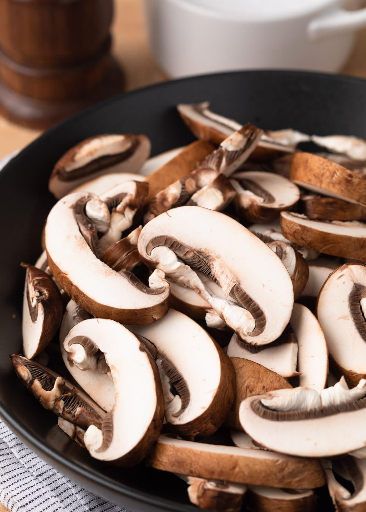 sliced cremini mushrooms in a dark gray matte bowl