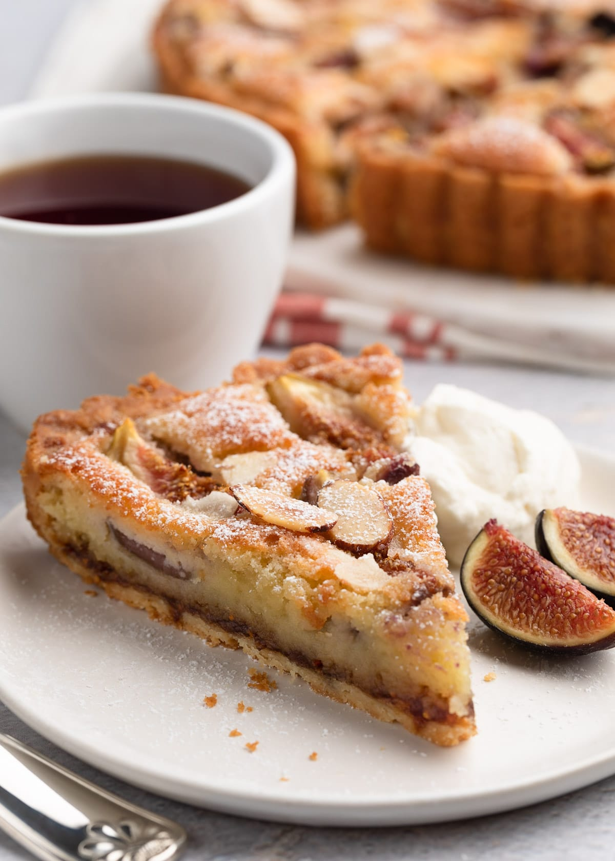 slice of fig and almond cream tart on a white plate with honey whipped cream and fresh sliced figs