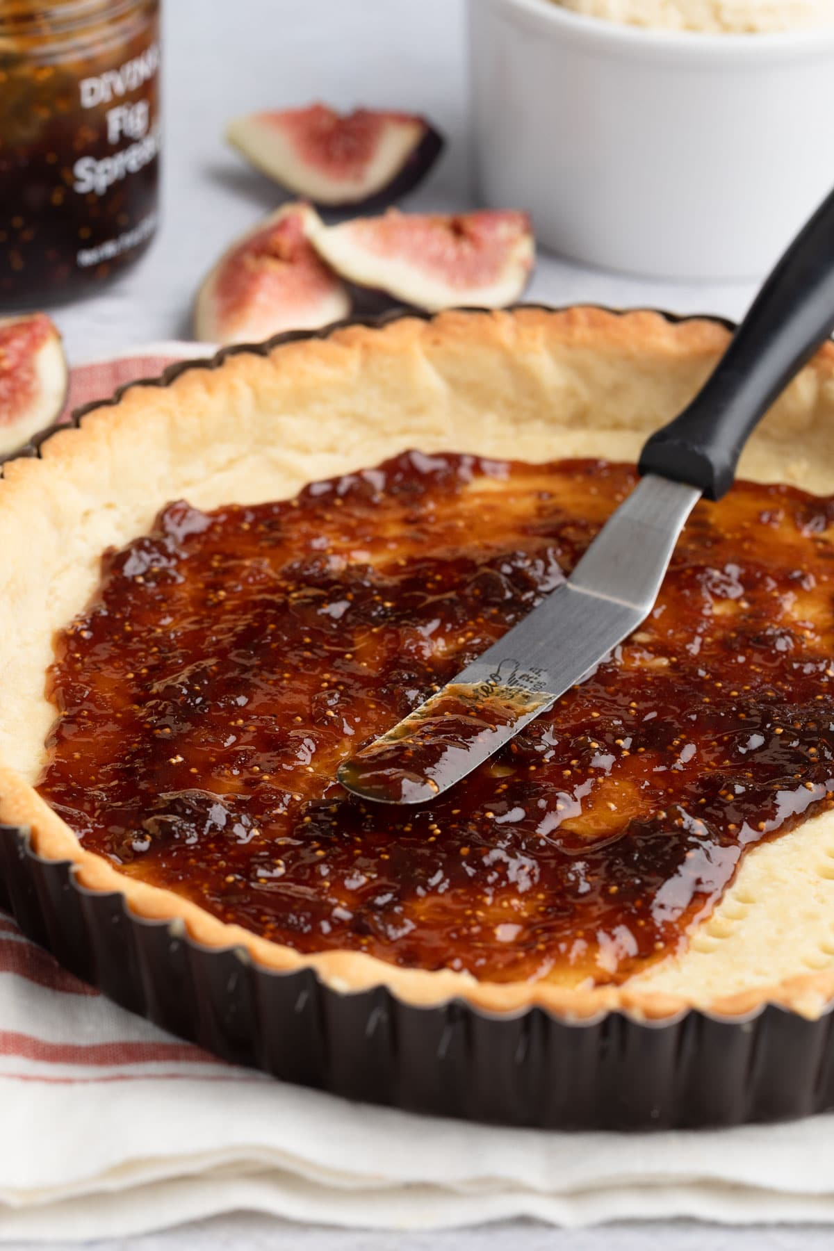 fig spread in a par-baked tart shell with a metal spreader