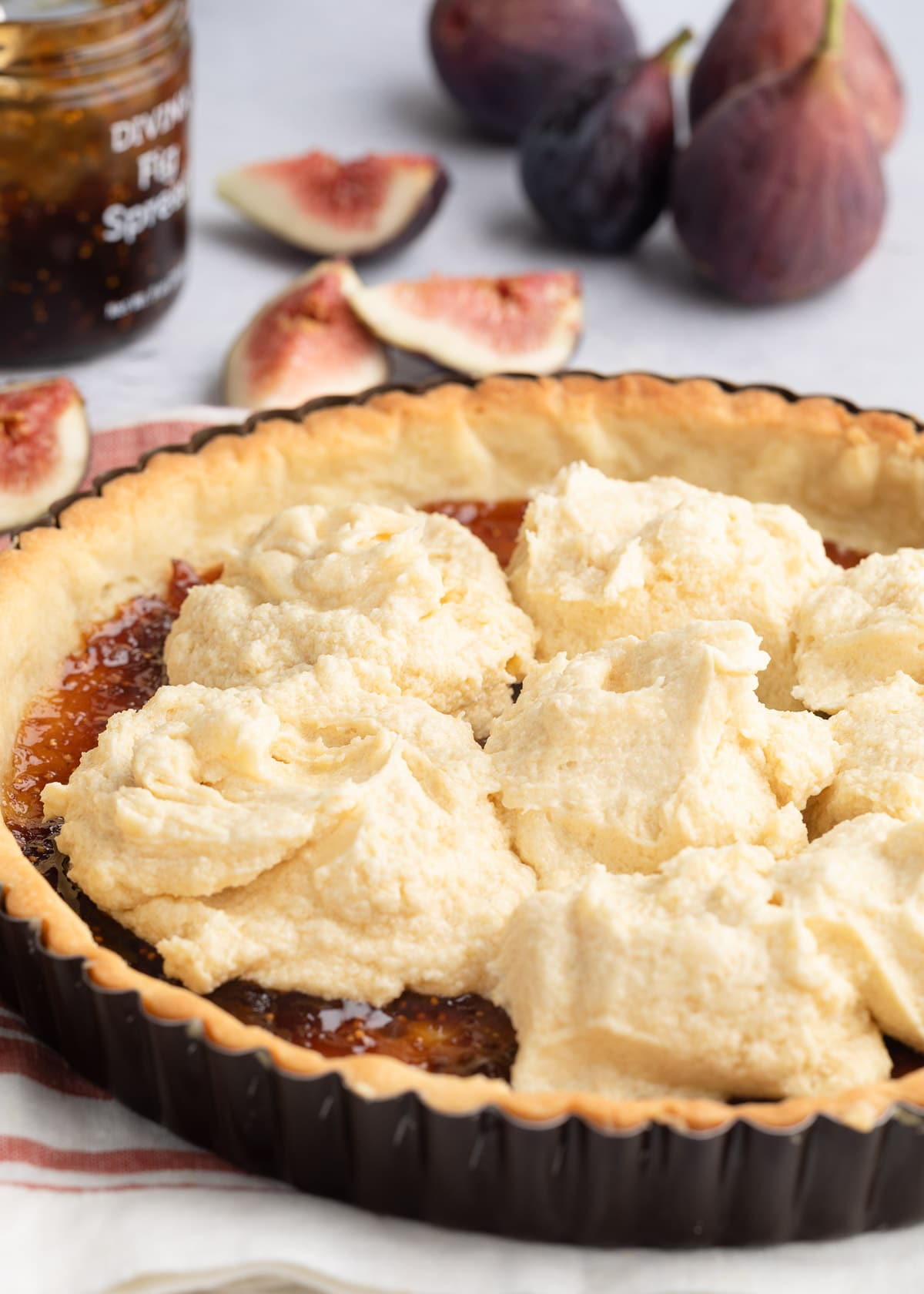 dollops of almond cream in a par-baked tart shell spread with fig jam