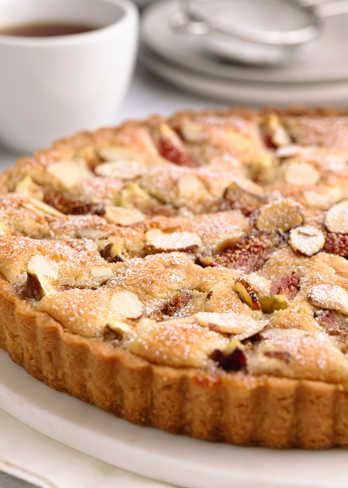 side view of a baked fig and almond cream tart on a white marble board