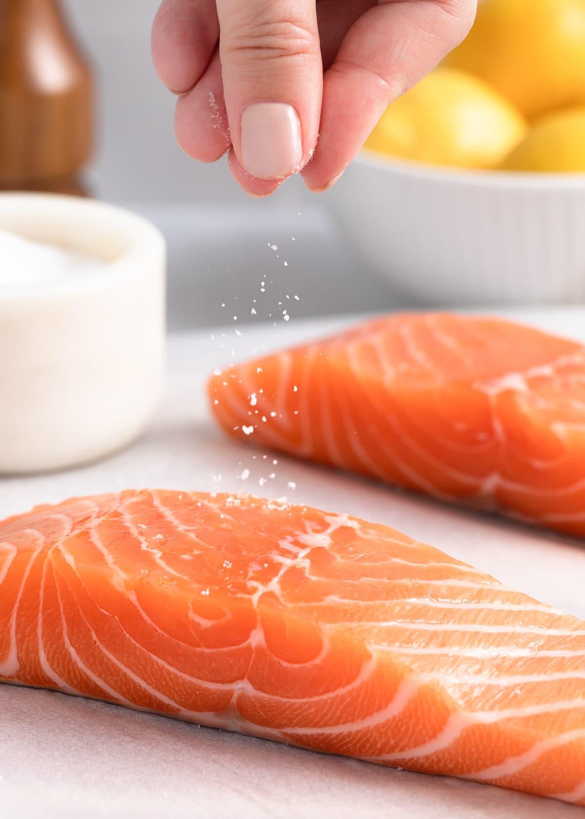 sprinkling salt onto a salmon fillet