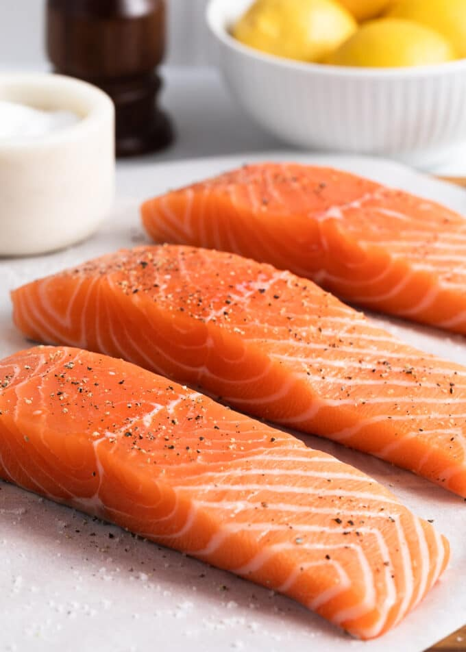 three raw salmon fillets on parchment paper seasoned with salt and pepper