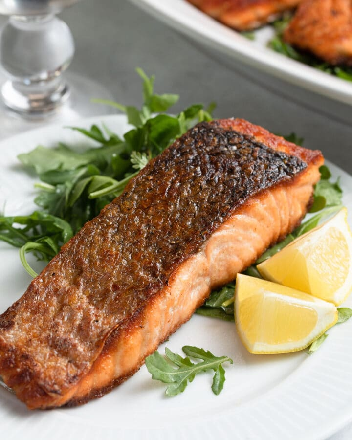 pan seared salmon on a white plate with arugula salad and lemon wedges