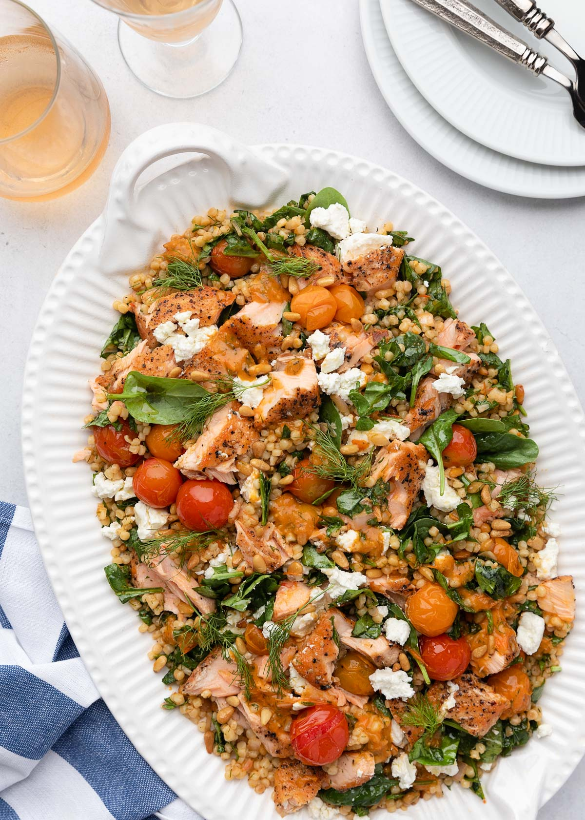salmon and couscous salad on a white platter next to a blue and white striped napkin