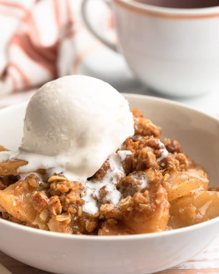 apple crisp in a white bowl with a scoop of vanilla ice cream and a cup of tea in the background